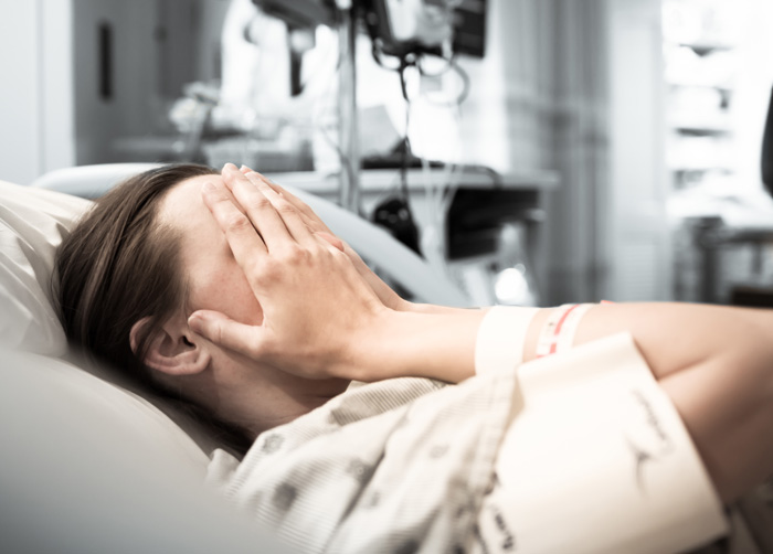 Can Withdrawal Be Fatal - girl in hospital bed with hands covering face