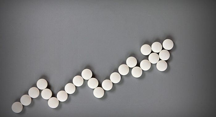 Abuse of Benzos Is on the Rise - white pills making arrow graph on grey background