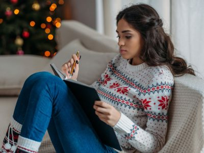 Understanding-How-the-Holiday-Season-Can-Affect-Your-Sobriety - woman in holiday sweater journaling