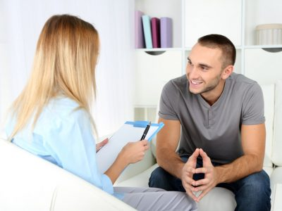 smiling man talking to female therapist