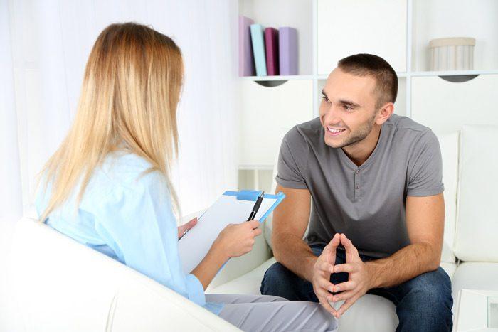 smiling man talking to female therapist