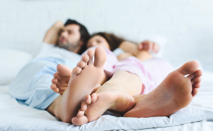 close up of feet, man and woman in bed