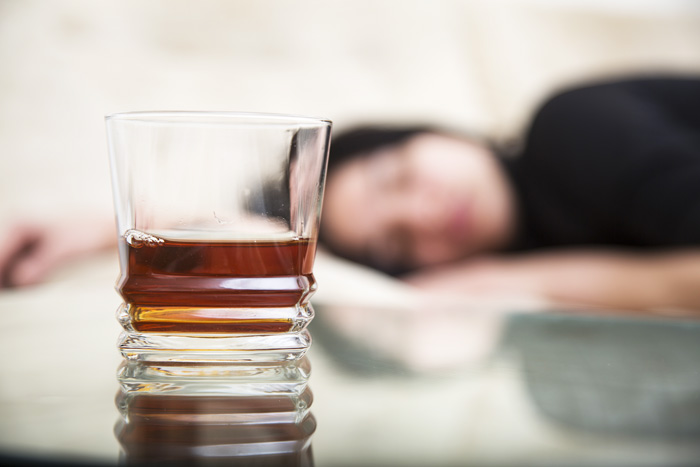 glass of liquor with girl laying down in background