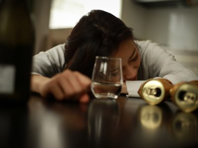 girl passed out at table surrounded by empty alcohol containers - drinking