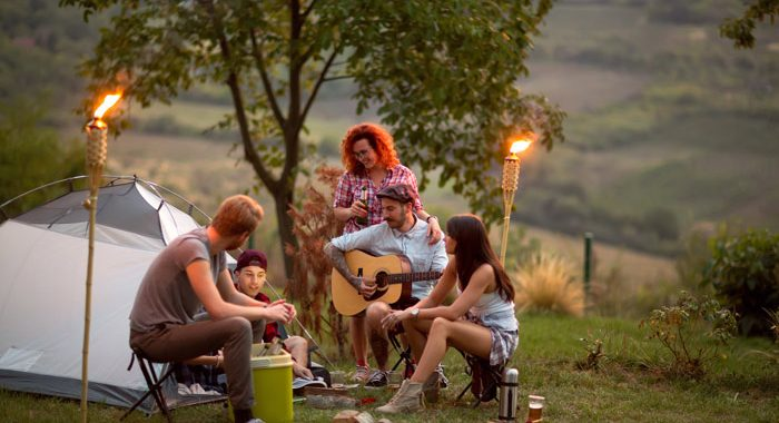 group of young friends camping at dusk, drinking and playing guitar - turn down alcohol