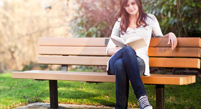 young brunette woman on park bench reading a book - depression and anxiety