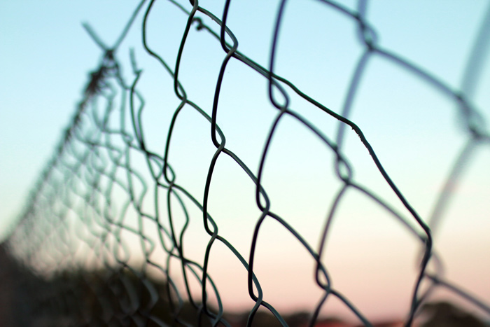 closeup of chain link fence with sunset in background - fears