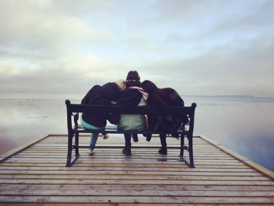 three friends sitting closely on bench on pier - drinking problem