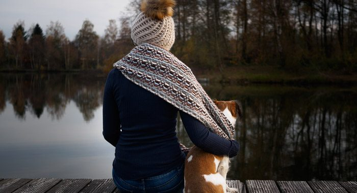 woman sitting on dock with her arm around her dog, facing away from the camera - mindfulness
