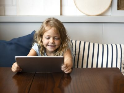 cute little girl smiling holding tablet computer at a table - young children