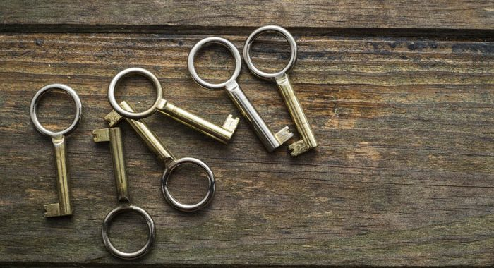 6 old fashioned metal keys laying on wooden table - life