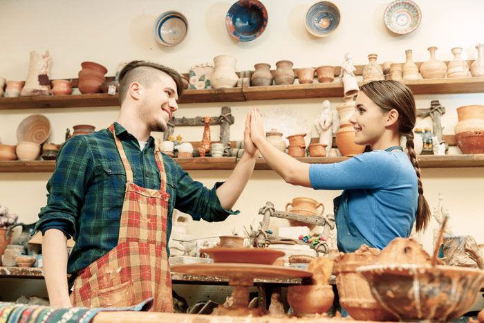 happy young couple at pottery workshop giving each other a high-five - Charleston