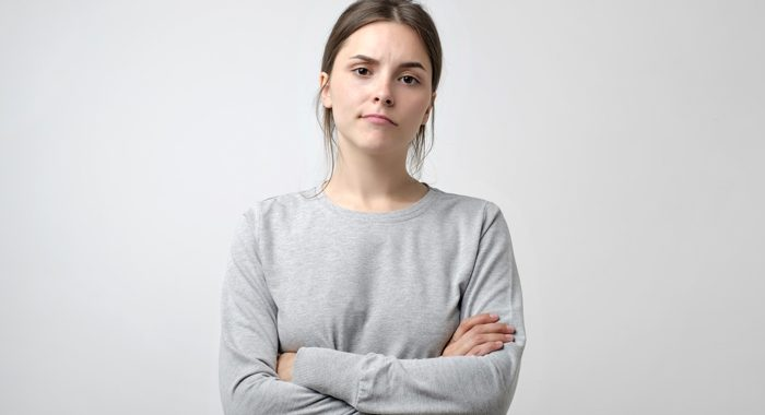 young woman with arms crossed on gray background - excuses