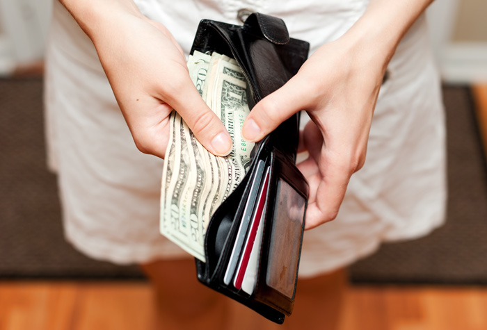 closeup of woman taking bills out of wallet - enabling