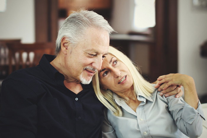 senior couple talking on couch - your recovery