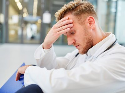 male doctor looking stressed sitting on ground - professionals
