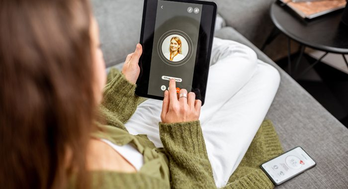 woman using tablet computer at home to video call doctor - telemedicine - telehealth - addiction recovery