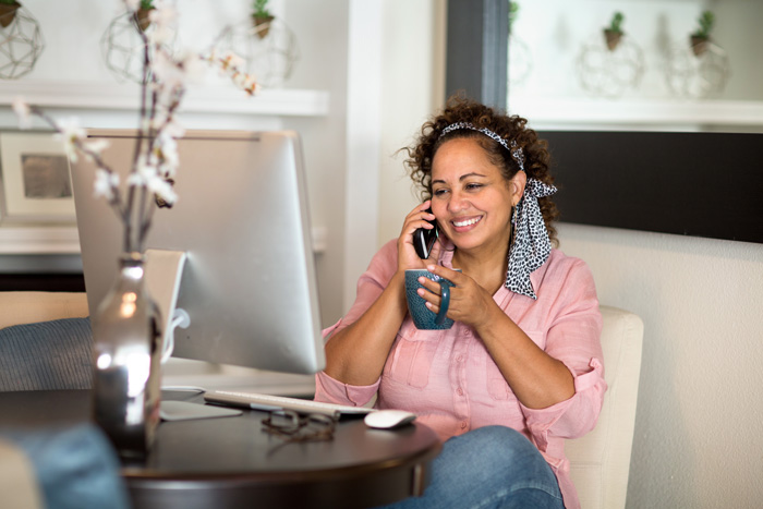 woman sitting at home in front of computer on cell phone drinking coffee - your loved one - pandemic