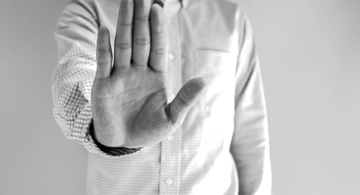 black and white image of man holding his hand out in a stop gesture - HALT - COVID-19