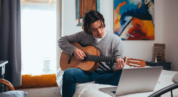 young man sitting in room practicing guitar - creative side
