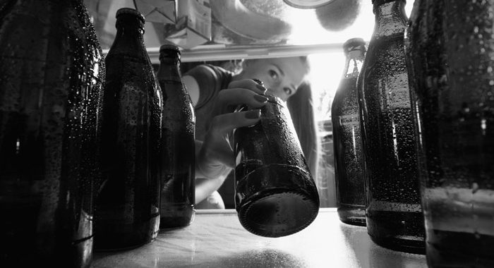 black and white image of woman reaching for a beer in refrigerator full of beer bottles - blackouts