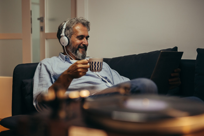 older man at home drinking coffee and listening to music