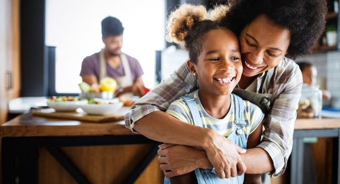 beautiful Black family - smiling mom hugging young daughter from behind in the kitchen