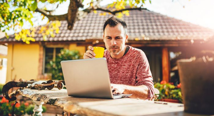 man working on laptop in backyard on sunny day - spending time in nature