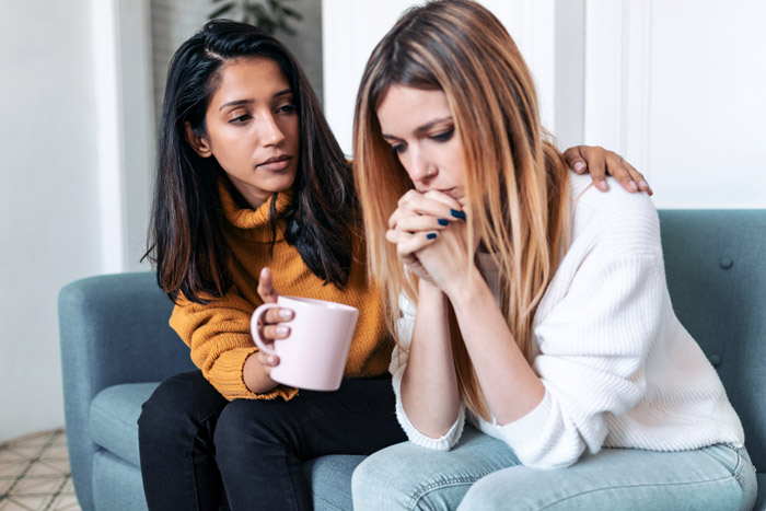 young woman consoling her friend - hydrocodone addiction