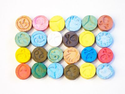 colorful, different ecstasy tablets lined up on white background
