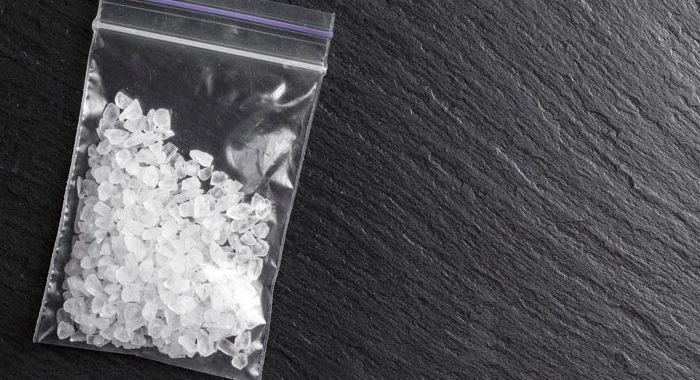 baggie of clear white crystals on slate background - meth addiction