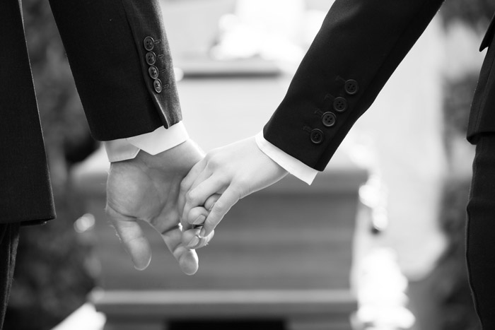 black and white image of two people holding hands in front of a casket - overdose