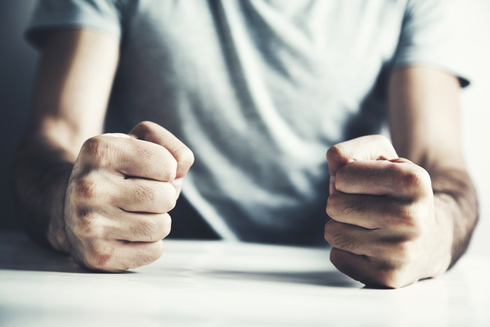 cropped shot of person sitting at a table with their clenched fists resting on the table top - anger