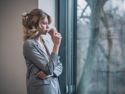 pretty young businesswoman looking out window drinking coffee - willpower and recovery