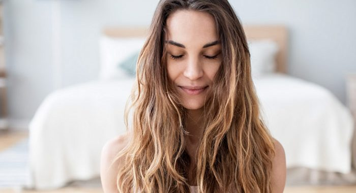 pretty young woman with long hair sitting on the floor of her room with her eyes closed - grounding techniques
