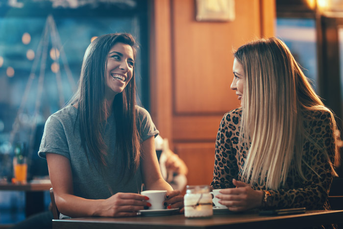 two pretty young women talking and having coffee - friendship and support - burnout