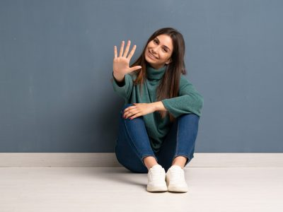 pretty young brunette woman sitting on the ground holding her hand out to signal the number five - myth