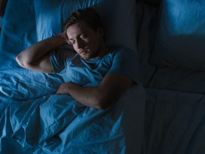 dark cool toned image from above of man sleeping in his bed - sleep hygiene